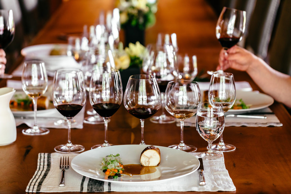 table setting with wine glasses and a Playful Plates food course